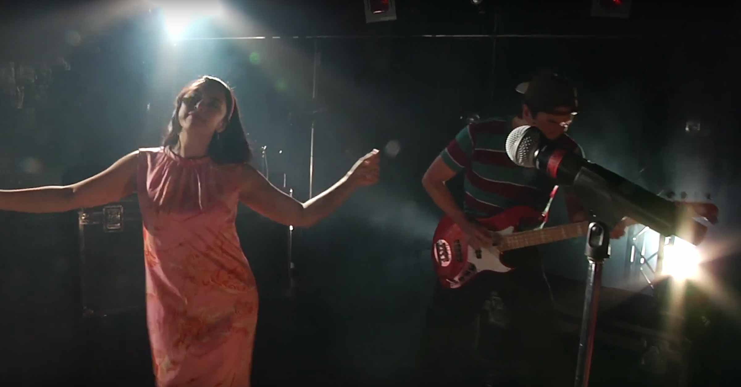Aja Wiltshire dancing next to Greg Watanabe, who is playing the guitar