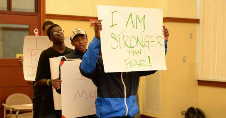 "Four young people stand in a line with signs in hand. The front sign reads ""I am stronger than fear!"""