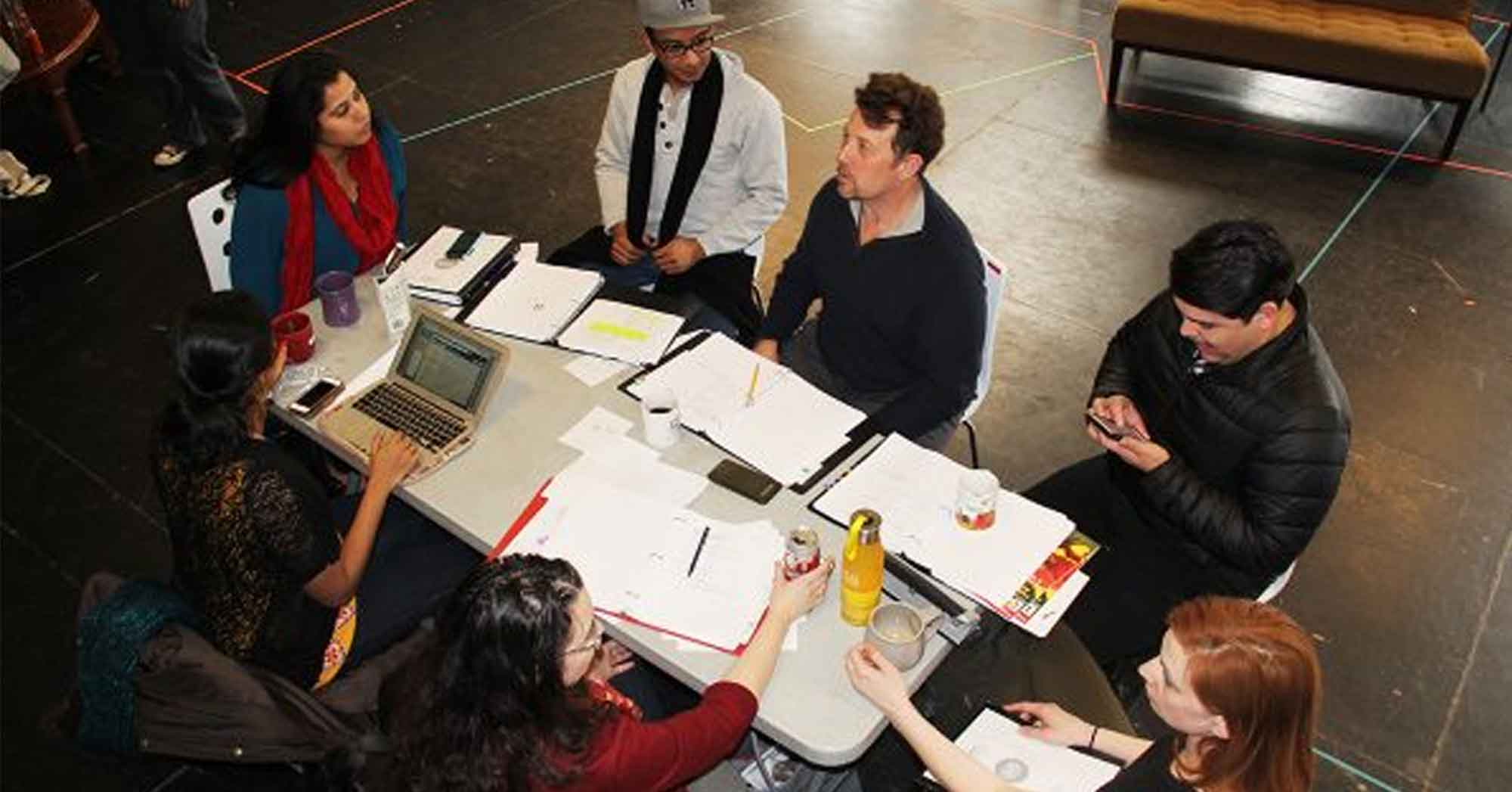 Group of artists sitting around a rectangular table discussing ideas