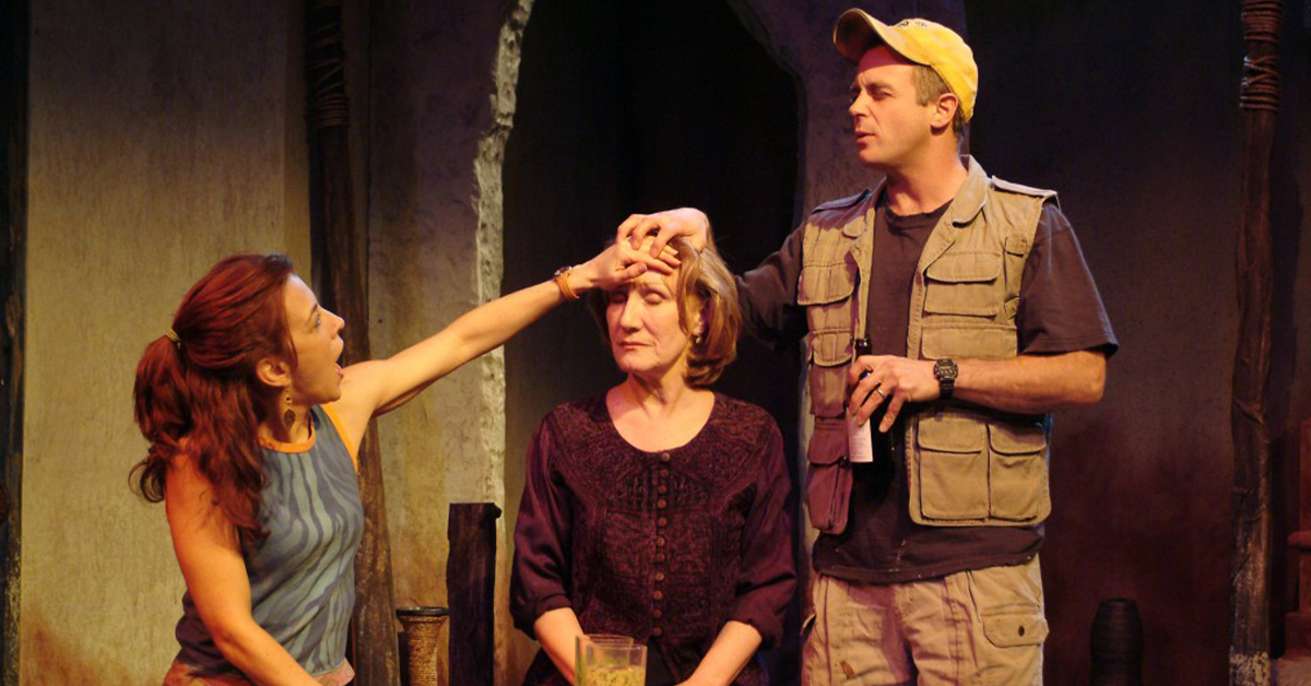 David Eigenberg and Jennie Moreau placing their hands on Peggy Roeder's forehead
