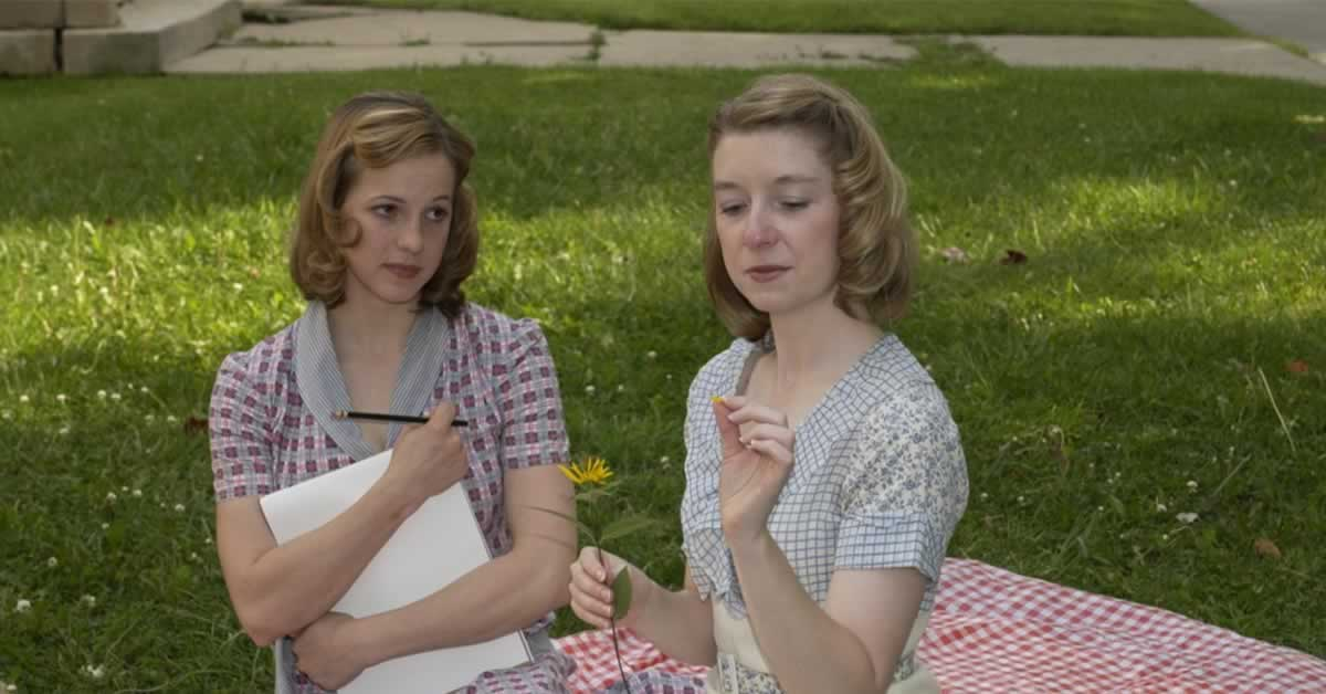 Mattie Hawkinson sitting on a picnic blanket with Bethanny Alexander, who is picking petals off a flower