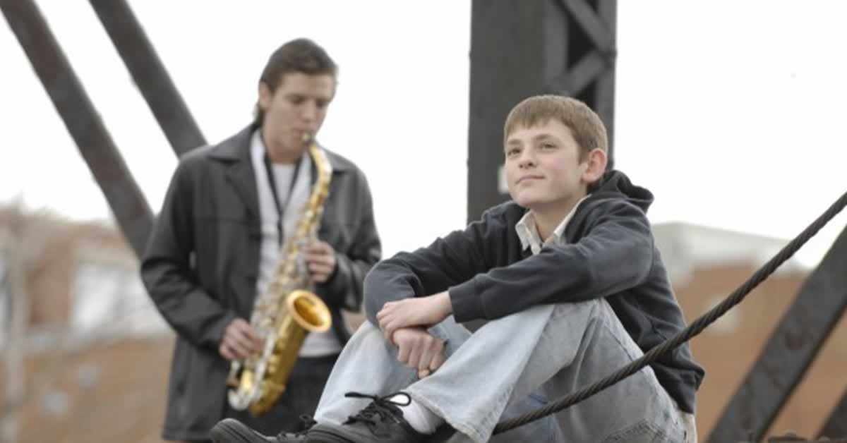 A man plays a saxophone while a young boy sits