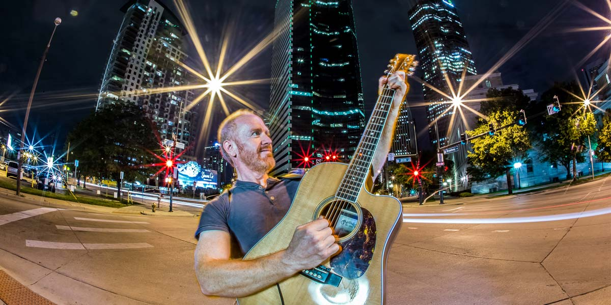 Mike Massé playing the guitar surrounded by the bright lights of the city