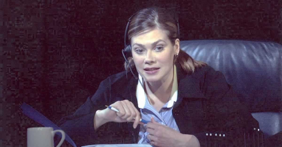 Melissa Carlson sitting with a headset on, holding a pen in her hand