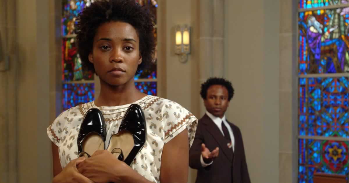 Linara Washington holding a pair of shoes to her chest while Kenn E. Head stands in the background