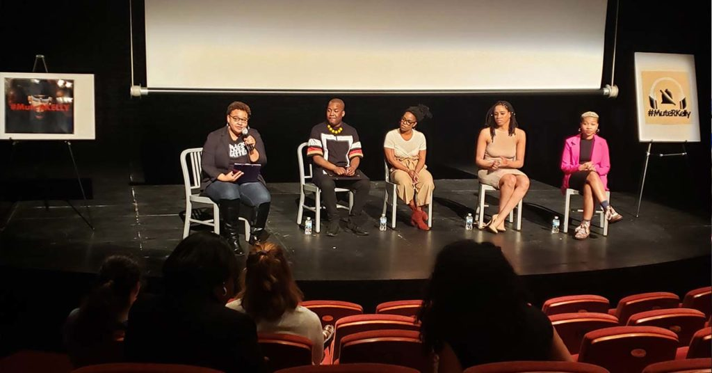 Five people sitting and speaking onstage during a Social Justice discussion