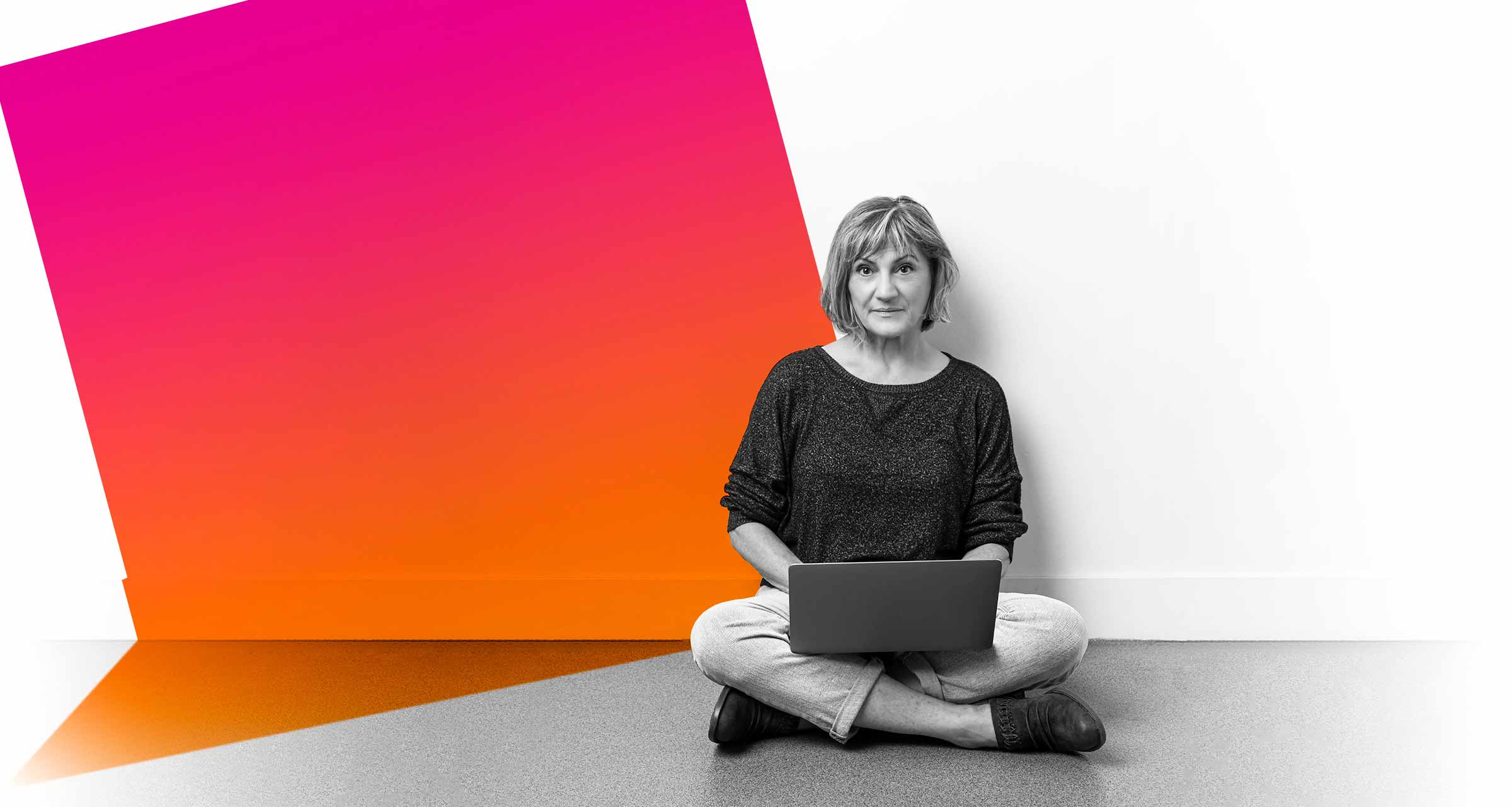 Janet Ulrich Brooks seated on the floor with a laptop computer on her lap