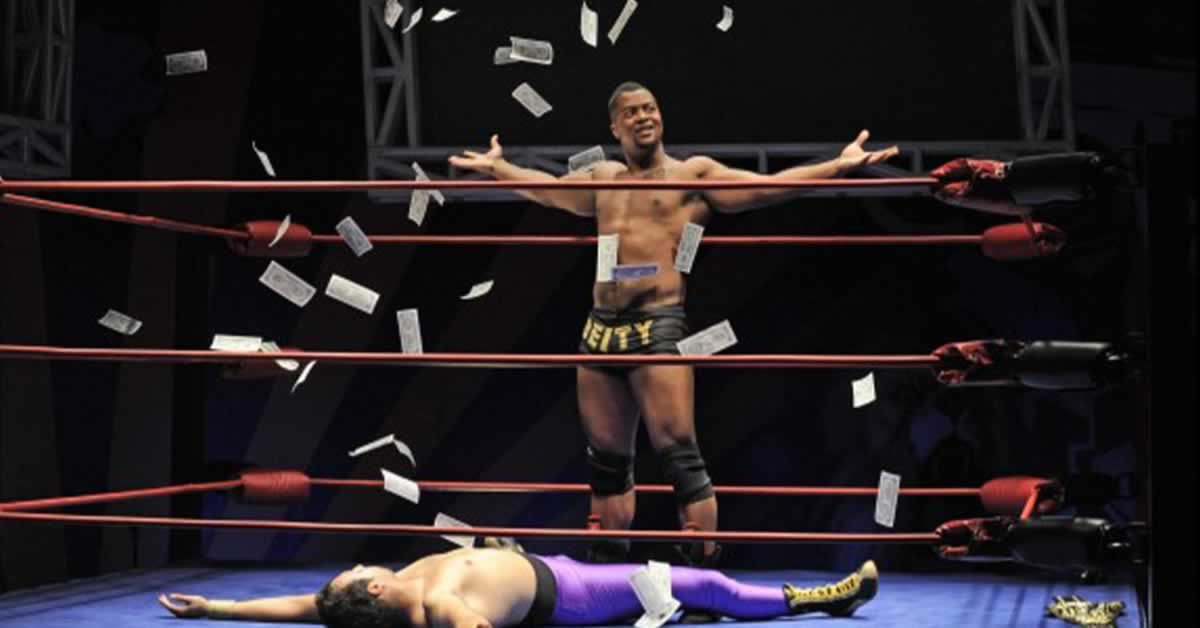 Kamal Angelo Bolden in a wrestling rink surrounded by money. His opponent lays on the ground
