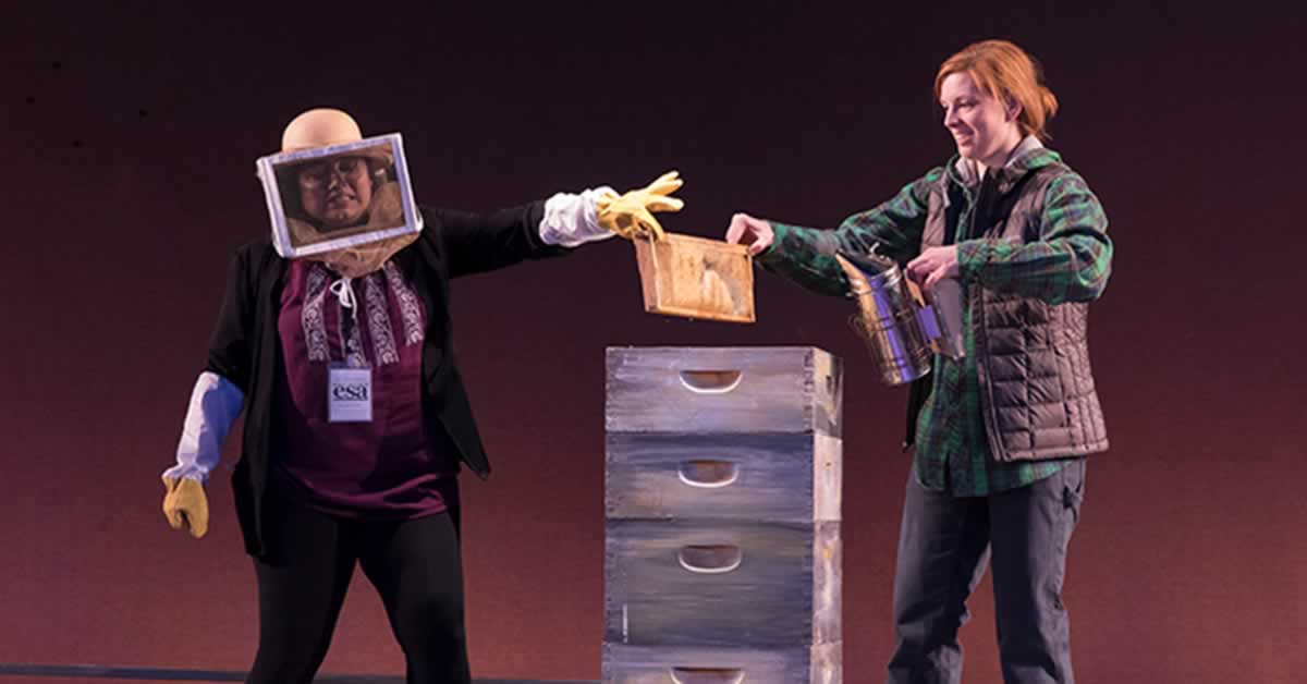 Darci Nalepa and Priya Mohanty holding a beehive. Priya Mohanty is dressed in a beekeeper outfit.
