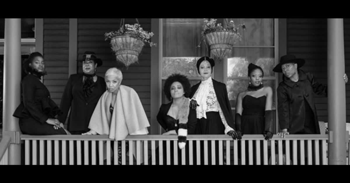 Linda Bright Clay, Diana Coate, Aneisa Hicks, Angela Alise, Lizan Mitchell, Penelope Walker and Jacqueline Williams standing on a front porch